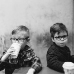 Two young brothers having a warm drink in coffee shop