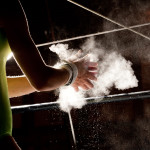 Chalk Power Flies As Female Gymnast Preps for Bars